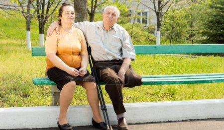 Photo pour Couple doux parler et assis sur le parc du banc - image libre de droit