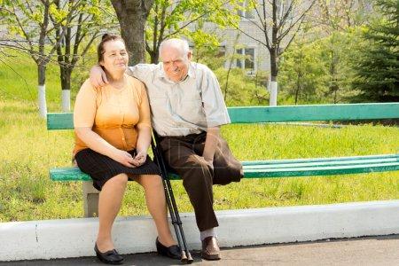 Photo pour Heureux couple assis sur un banc et de parler dans le parc - image libre de droit