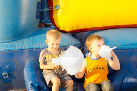 Young boys happily sharing a large cotton-candy