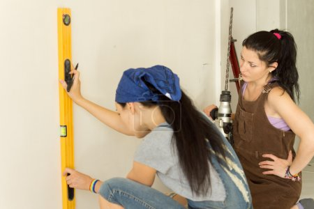 Woman marking a vertical line on a wall using a ma...