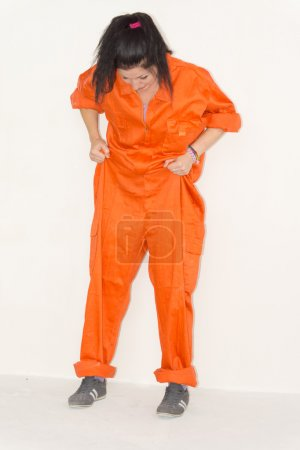 Woman in outsized orange overalls