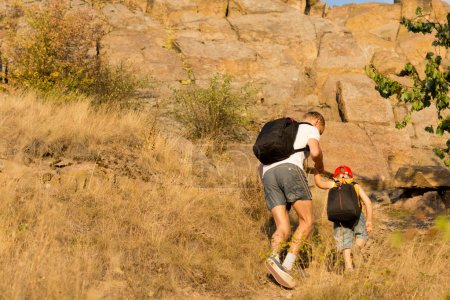 Man helping a young boy hiking on a mountain