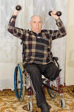 Photo pour Amputé mâle supérieur travaillant à soulever des poids dans son fauteuil roulant possède une paire d'haltères au-dessus de sa tête pour tonifier ses muscles - image libre de droit