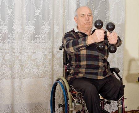 Photo pour Senior handicapé homme exerçant avec une paire d'haltères pour renforcer ses bras tout en étant assis dans un fauteuil roulant - image libre de droit
