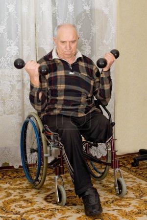 Photo pour Principal désactivé un homme assis dans son fauteuil roulant exercice avec des haltères avec un regard de détermination sur son visage car il soulève des poids pour renforcer ses muscles du bras - image libre de droit