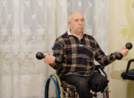 Photo for Senior handicapped male amputee sitting in his wheelchair doing exercises working out with a pair of dumbbells - Royalty Free Image