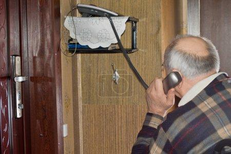 Elderly man talking on a telephone