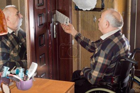 Photo pour Désactivé le vieillard en fauteuil roulant collecte son journal qui a été diffusé par le biais de sa porte avec lui se reflète dans le miroir aux côtés - image libre de droit