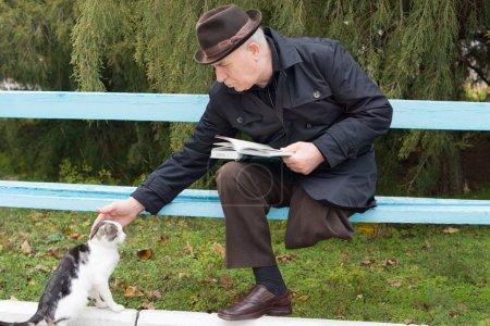 Photo pour Personnes âgées handicapées homme avec séance amputé une jambe sur un banc de parc avec son livre descendant et caressant un chat - image libre de droit