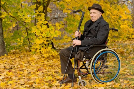Photo pour Homme senior handicapé en fauteuil roulant assis dans son manteau et chapeau dans un boisé automne coloré, tenant ses béquilles dans sa main, avec fond - image libre de droit