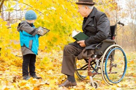 Photo pour Handicapé homme aîné avec une jambe amputée, assis dans un manteau chaud et un chapeau dans son fauteuil roulant dans un parc d'automne coloré je regarde son petit-fils jouer sur son ordinateur tablette - image libre de droit