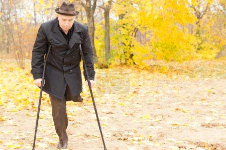Photo pour Vieux Monsieur handicapé avec une jambe amputée marchant avec des béquilles dans un parc d'automne avec le feuillage jaune coloré - image libre de droit
