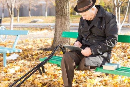 Photo pour Retraité handicapée avec une jambe amputée assis sur un banc de parc dans le soleil d'automne dans un manteau et chapeau à l'aide d'une tablette PC - image libre de droit