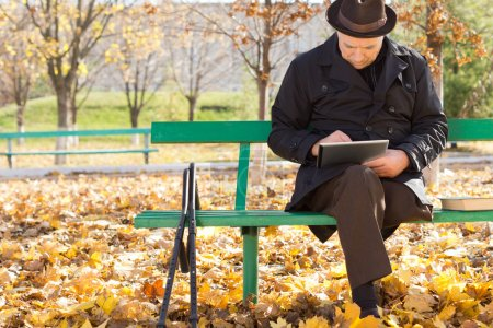 Photo for Elderly man on crutches using a tablet computer as he sits outdoors in the sunshine in a warm overcoat on a chilly autumn day - Royalty Free Image