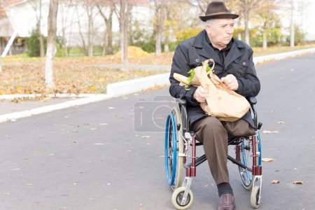 Elderly man in a wheelchair doing grocery shopping