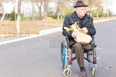 Photo pour Vieillard en fauteuil roulant ramener à la maison les produits d'épicerie au supermarché dans un sac de papier brun reste assis en attente dans la rue pour assistance - image libre de droit