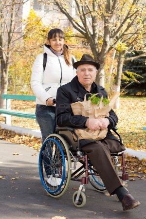 Photo pour Un aîné handicapé fait ses courses avec l'aide d'une jolie femme souriante qui pousse son fauteuil roulant le long de la rue alors qu'il tient le paquet d'épicerie - image libre de droit