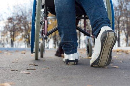 Foto de Bajo ángulo vista de cerca de los pies de una persona empujando una silla de ruedas a lo largo de una calle asfaltada - Imagen libre de derechos