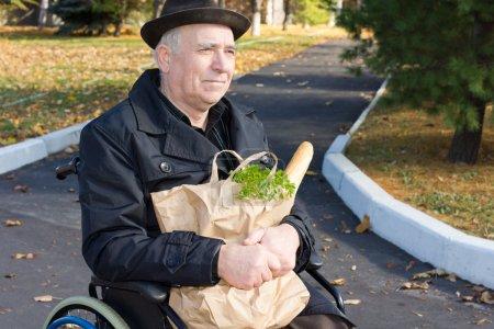 Photo pour Souriant vieux monsieur assis dans un fauteuil roulant dans la route avec son sac de papier brun d'épicerie saisi dans ses bras - image libre de droit