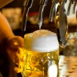 Close up of the hand of a man pouring a tankard of frothy draught beer from a stainless steel beer tap in a bar or pub into a large glass tankard