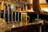 řádek kohoutků připojené k kovové pivních sudů v baru