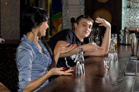 Photo pour Jeune homme et jeune femme contestant le dernier verre de vodka dans le bar avec la femme gesticulant et l'homme pointant du doigt comme ils décident qui va l'avoir - image libre de droit