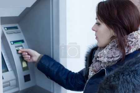 Woman retrieving her bank card at the ATM