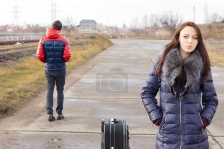 Young woman waiting with her suitcase
