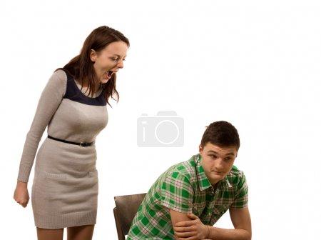 Photo pour Jolie jeune femme debout criant à son petit ami reste assis dans un fauteuil avec une expression résignée, isolé sur blanc - image libre de droit