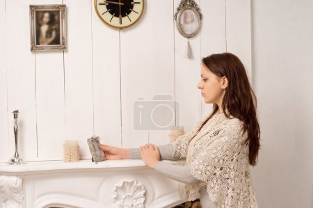 Photo for Elegant young woman standing with her arms resting on a marble fireplace staring at on old portrait in a silver frame as she reminisces or pays tribute to a loved one - Royalty Free Image
