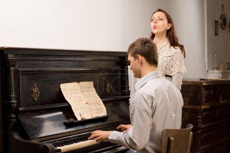 Photo pour Jeune couple pratiquant un duo musical avec une belle jeune femme chantant le chant accompagné d'un jeune homme jouant du piano - image libre de droit