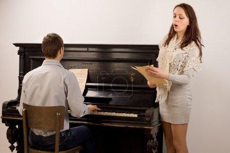 Photo pour Jeune couple donnant un duo classique avec une élégante jeune femme séduisante, chantant à partir d'une partition de musique accompagnée d'un jeune homme sur un piano - image libre de droit