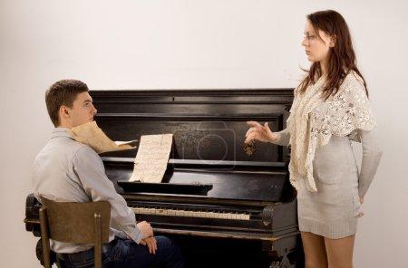 Photo pour Jeune couple pratiquant un duo classique, une pause pour une discussion comme la jolie chanteuse soulève un problème avec le jeune pianiste mâle - image libre de droit