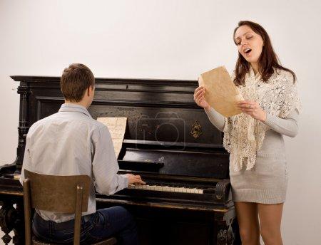 Photo pour Jeune femme chantant un permanent de la chanson en solo aux côtés d'un jeune homme jouant un chant piano droit avec plaisir évident - image libre de droit