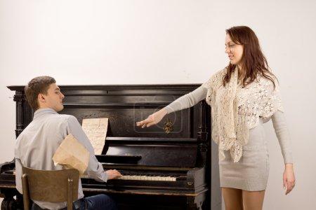 Photo pour Jeune femme reconnaissant le pianiste à la fin de sa prestation de chant solo, jetant de côté sa note car elle tend la main à lui - image libre de droit
