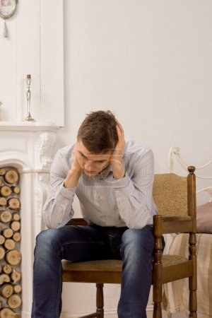 Photo pour Jeune homme assis pensant dans un vieux fauteuil en bois devant une cheminée en marbre dans le salon frottant son cou alors qu'il essaie de trouver une réponse - image libre de droit