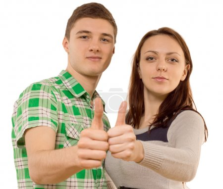 Confident young couple showing thumbs up, on white