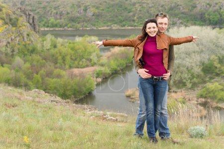 Photo pour Joyeux couple romantique célébrant une journée agréable à la campagne avec l'homme embrassant la femme par derrière alors qu'elle sourit avec les bras tendus surplombant une vallée pittoresque et une rivière - image libre de droit