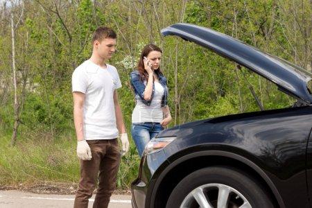Photo pour Jeune couple téléphone pour l'assistance routière après leur voiture est tombé en panne debout regardant dans le compartiment moteur avec le capot vers le haut - image libre de droit