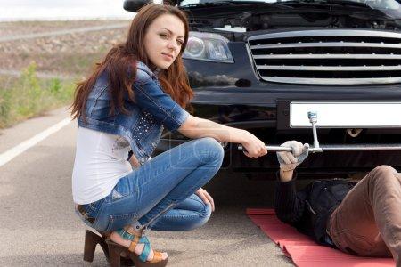 Woman kneeling in front of her broken down car