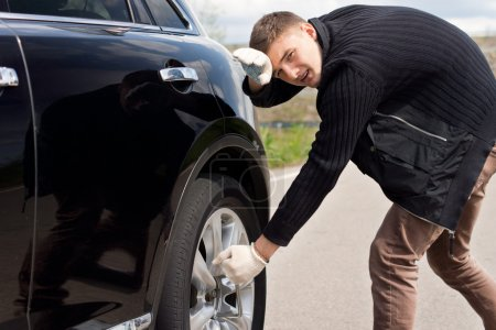 Young man battling to change the tyre on his car