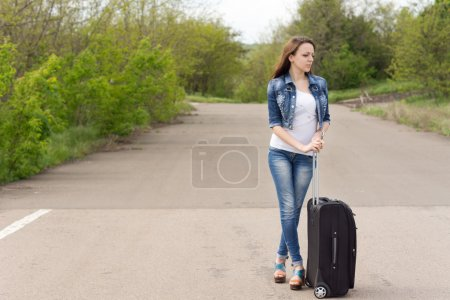 Woman waiting with her suitcase in the road