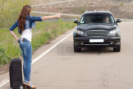 Trendy woman hitchhiking on a