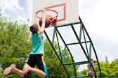 Young teenager dunking a basketball