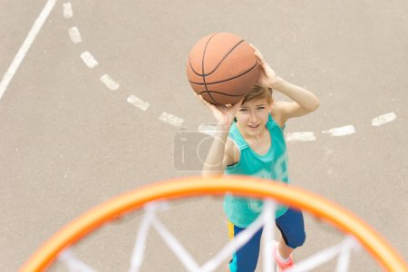 Teenage girl playing basketball
