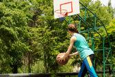 Sporty slender teenager playing basketball