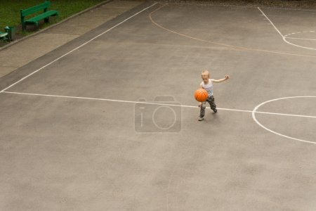 Small boy playing basketball bouncing the ball