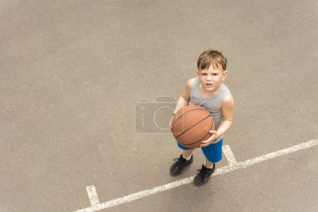 Little boy with a basketball looking puzzled