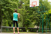 Athletic slender young girl playing basketball