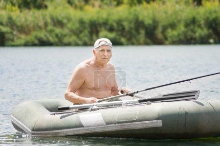 Smiling senior fisherman enjoying a day on a lake